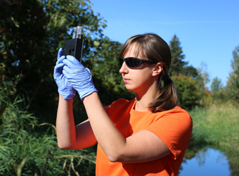 Katie Holzer checks water samples as part of her Environmental Services career.